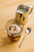 Glass with ice black coffee on wooden table with milk pitcher and spoon