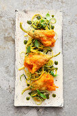 Baked courgette flowers filled with tomato polenta on zoodles