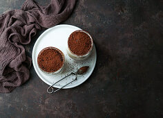 Rraditional coffee flavored dessert tiramisu served in glass cup on table