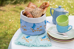 Bread basket and linen napkins decorated with bird motifs