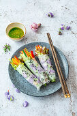 Vegan spring rolls with edible flowers in rice paper and green chili dip