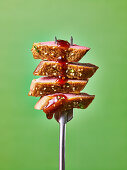 Cooked duck on a fork with sauce dripping, against a green background