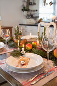 Conifer branches and apples arranged on festively set table