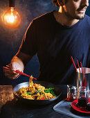 Man eating stir-fried spicy noodles