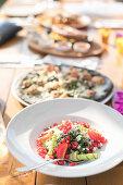 Gemüsesalat mit Granatapfel und Kräutern, Pizza und Snacks