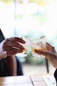 Mann und Frau stossen mit zwei Whiskeygläsern an