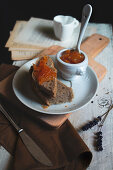A slices of handmade bread with homemade kumquat marmelade on the wood table