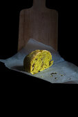 A piece of hand made bread with turmeric and walnuts on the black backdrop