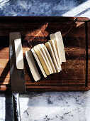 Slicing fresh pressed tofu on a dark wooden board
