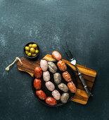 Spanish sausages on the cutting board (butifarra blanca, chorizo, morcilla de cebolla)