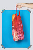 Hand carrying net bag with various groceries against blue rectangle during zero waste shopping