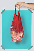 Hand carrying red string sack with glass containers of dairy against turquoise rectangle during eco friendly shopping