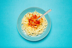 Blue ceramic plate with pasta and tomato sauce on light blue background