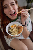 Cheerful redhead female laughing blinking eye and picking noodles from bowl of tasty ramen while sitting on couch at home