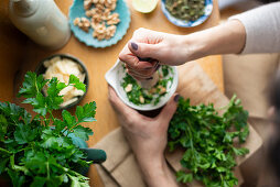 Pesto verde with parsley and mint being made in a mortar