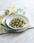 Spinach gnocchi with cheese sauce, ham and flaked almonds