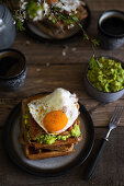 Waffles with avocado, bacon, fried egg and maple syrup