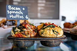 Savoury muffins with bacon and spinach on a restaurant counter