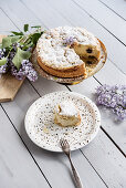 Blueberry crumble cake on a golden cake stand, sliced
