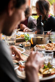 People eating around the table, focus on the food and blurred people