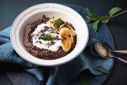 Vegan chocolate semolina porridge with soy yogurt, fried banana and mint