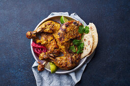 Marinated tandoori chicken with naan, limes and coriander (India)