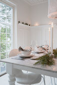 Set table in white dining room decorated for Christmas