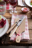 Cloth napkin with wooden boards and cutlery on a rustic table