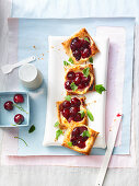 Square puff pastry tarts with vanilla cream and cherries