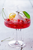A cherry cocktail with gin, ginger ale and mini wild cherries