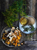 Freshly picked wild mushrooms with herbs on a wooden table