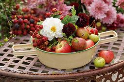 Bowl of apples, dahlias and unripe blackberries
