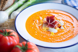 Traditional spanish salmorejo - cold tomato soup served with boiled egg, iberico ham and olive oil