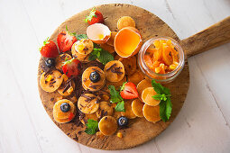 Minipancakes with siroup, strawberries, blueberries, candied orange and chocolate