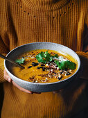 Woman holding spice-roasted pumpkin soup with macadamia dukkah