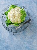 A cauliflower in a metal basket