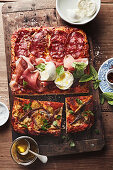Pizza taglio with prosciutto, salami, anchovies and mozzarella