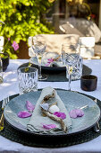 Summer table setting with mussel shells and rose petals