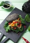 Vegan black burger with mock duck, Asian salad and grilled vegetables