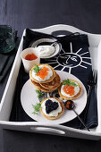 Blinis with caviar and sour cream on tray