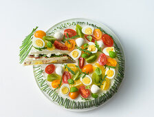 Sandwich cake with colourful cherry tomatoes and quail's eggs