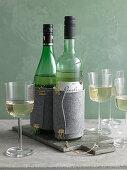 Wine bottles in felt cooling sleeves