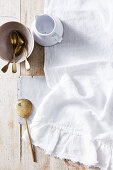 Crockery, cutlery and a cloth on a wooden surface