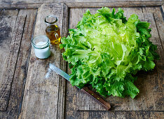 Endive salad on a wooden background with a knife, oil carafe and salt
