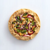 Onion tart with peaches, rosemary, goat's cheese and pistachio nuts