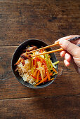 Hands taking Chinese vegetable and duck stir fry with chopsticks