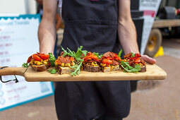 A person serving open sandwiches with salami, tomatoes and rocket on a wooden board