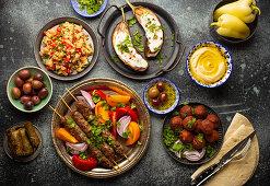 Nahöstliches Abendessen mit Kebab, Falafel, Taboule, gegrillten Auberginen, Oliven und Hummus
