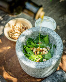 Ingredients for lovage pesto in a mortar