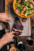 Grilled tomahawk steak on a wooden board with salad being served